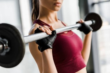 cropped view of concentrated sportswoman in weight lifting gloves training with barbell at gym