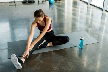 concentrated sportswoman sitting on mat and doing stretching exercise at gym