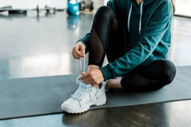 cropped view of sportswoman tying laces on training shoes while sitting on fitness mat at gym