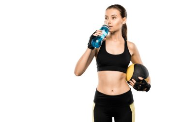 beautiful sportswoman drinking water from sport bottle and holding medicine ball isolated on white