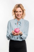 Photo beautiful businesswoman holding piggy bank and smiling at camera isolated on white