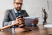 Detailní pohled na dřevěné kladivo a soudce pracovat s doklady za