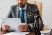 close-up view of lady justice statue and lawyer working working with papers behind
