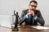 Fotografie Detailní pohled socha spravedlnosti lady a právník sedí za