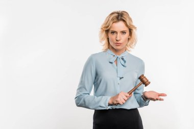 serious female judge holding wooden hammer and looking at camera isolated on white