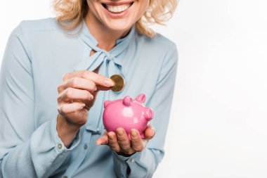 cropped shot of smiling businesswoman holding piggy bank and coin isolated on white