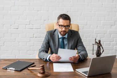 serious male judge working with papers and laptop in office
