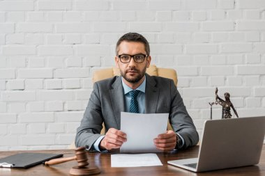 serious lawyer in eyeglasses working with papers and looking at camera in office