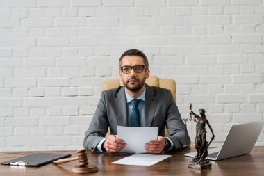 serious judge in eyeglasses working with papers and looking at camera in office