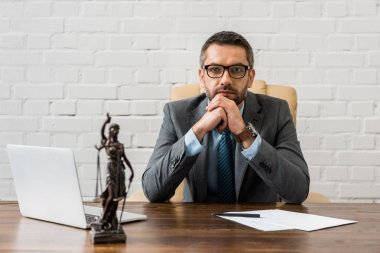 serious bearded lawyer in suit sitting at workplace and looking at camera