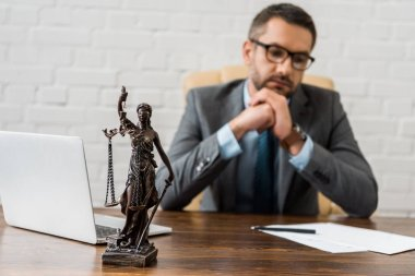 close-up view of lady justice statue and lawyer sitting behind