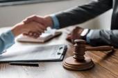 Fotografie Detailní pohled na dřevěné kladivo a advokáta s klientem třesoucíma se rukama za