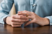 close-up partial view of woman taking off wedding ring, divorce concept