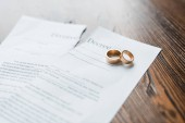 close-up shot of teared divorce decree and engagement rings on wooden table