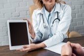cropped shot of female doctor showing tablet with blank screen to patient at office
