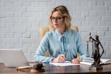 serious female judge in eyeglasses working with papers and using laptop at workplace