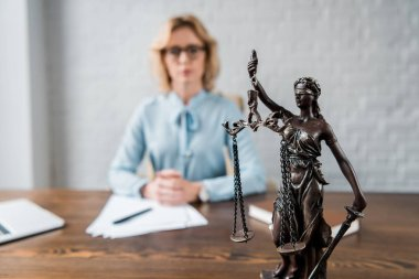close-up view of lady justice statue and female lawyer working behind