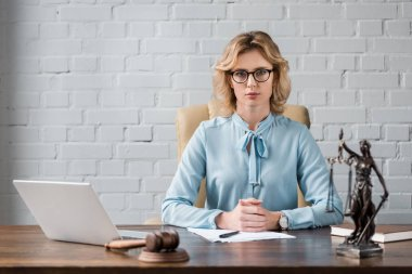 serious female lawyer in eyeglasses sitting at workplace and looking at camera