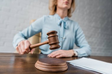 cropped shot of female judge holding wooden hammer at workplace