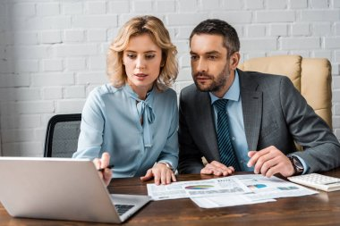 concentrated business partners working with documents and laptop together in office
