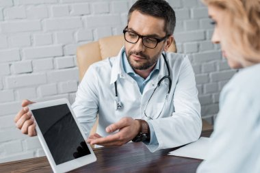 handsome doctor showing tablet with blank screen to patient at office