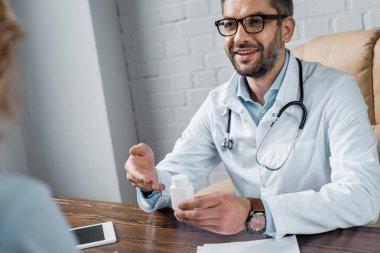 smiling doctor showing jar of medicines to patient at office