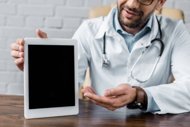 Cropped shot of doctor pointing at blank tablet at office stock vector