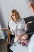 Fotografie confused woman having psychologist therapy session at office