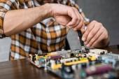 Fotografie Oříznout záběr počítačový inženýr opravy základní desky s šroubovák