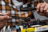 Oříznout záběr počítačový inženýr s pinzetou a zvětšovací sklo opravy základní desky