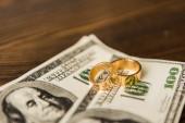 zblízka střílel hotovosti a snubní prsteny na dřevěný stůl