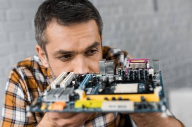 close-up portrait of handsome computer engineer with motherboard