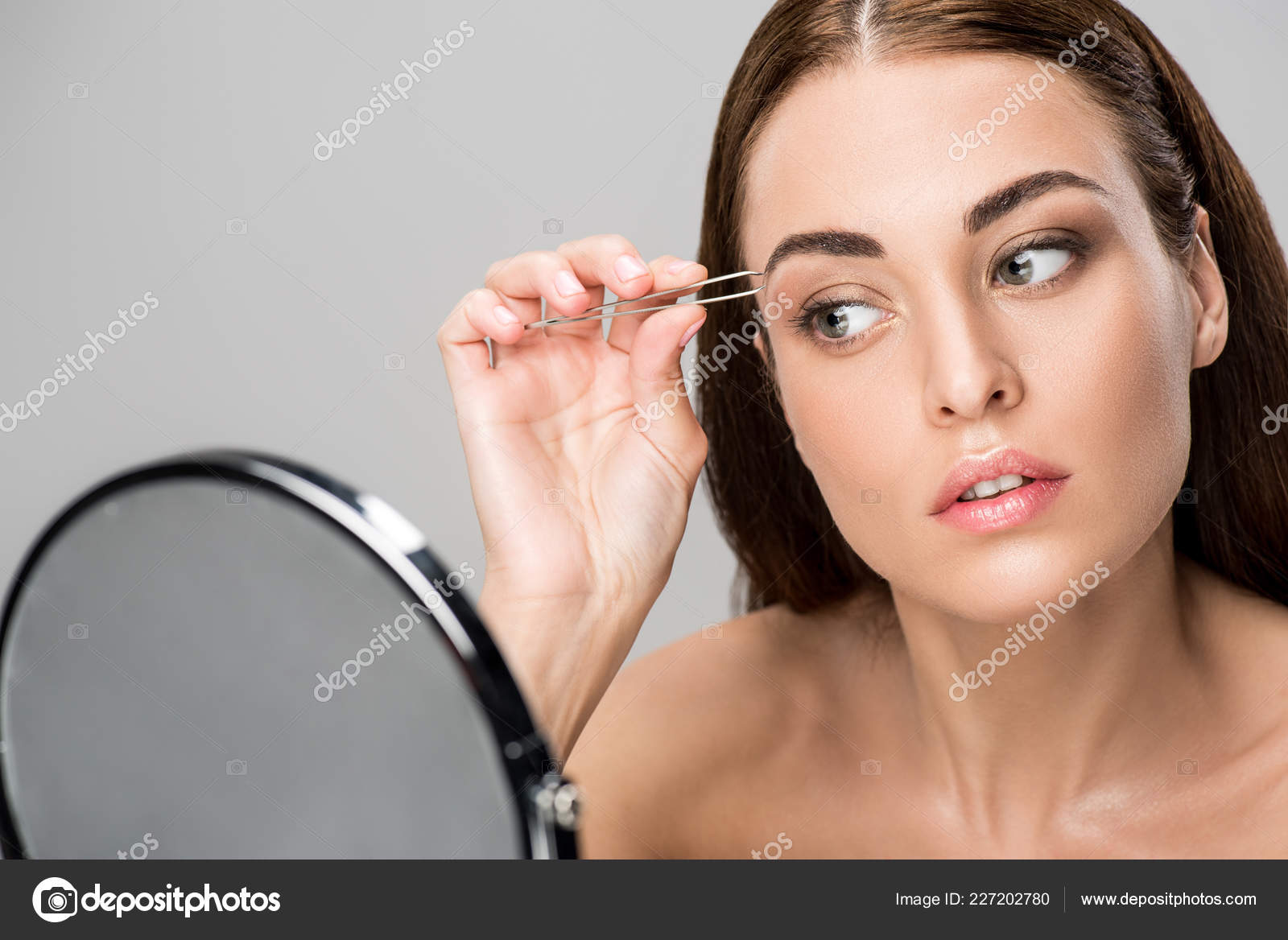 Young Woman Correcting Shape Eyebrows Looking Mirror Isolated Grey