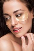 krásná mladá žena s kolagenu očních obvazů, izolované Grey