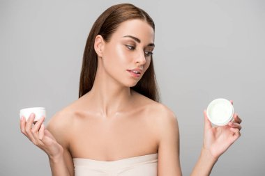 attractive girl choosing face cream, isolated on grey