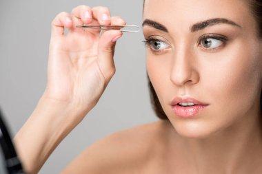 Beautiful girl correcting shape of eyebrows isolated on grey stock vector