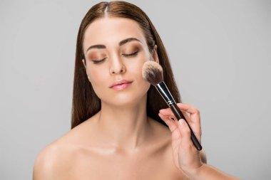 beautiful young woman applying face powder with cosmetic brush, isolated on grey