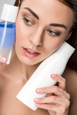 beautiful woman with clean face holding makeup remover bottles, isolated on grey