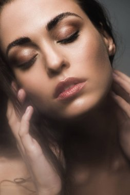 beautiful tender woman with closed eyes, isolated on grey