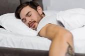 csinos fiatal szakállas alszik az ágyban