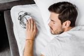 felülnézet fiatalember gazdaság ébresztőóra, és alszik az ágyban