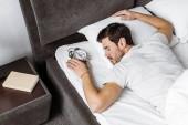 pohled z vysoké úhlu mladého muže drží budík a spí v posteli