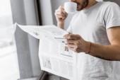 Oříznout záběr mladého muže, pití kávy a čtení novin v noci