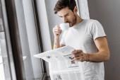 pohledný mladý muž popíjel kávu a čtení novin v noci