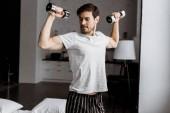 Fotografia giovane bello in pigiama allenamento con manubri e guardando i muscoli al mattino
