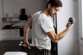 handsome young man in pajamas exercising with dumbbells and looking at biceps at home
