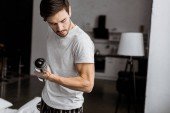 handsome young man holding dumbbells and looking at biceps at home