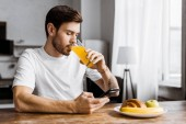 attractive young man using smartphone during breakfast at home