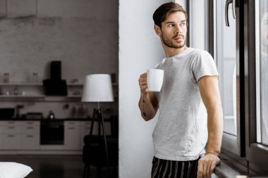 Attractive young man in pajamas with mug of coffee leaning back on window at home stock vector