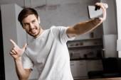 Fotografie hübscher junger Mann unter Selfie und Pistole Geste zu Hause
